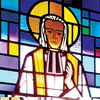 Stained glass window of Saint John Vianney bestowing a blessing