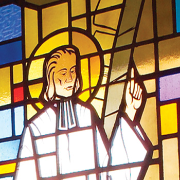 Stained glass window detail of Saint John Vianney preaching