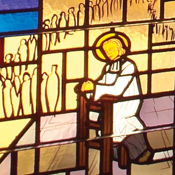 Stained glass window detail of Saint John Vianney in prayer