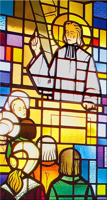 Stained glass window of Saint John Vianney preaching